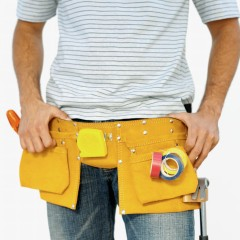 Mid section of a workman wearing a tool belt